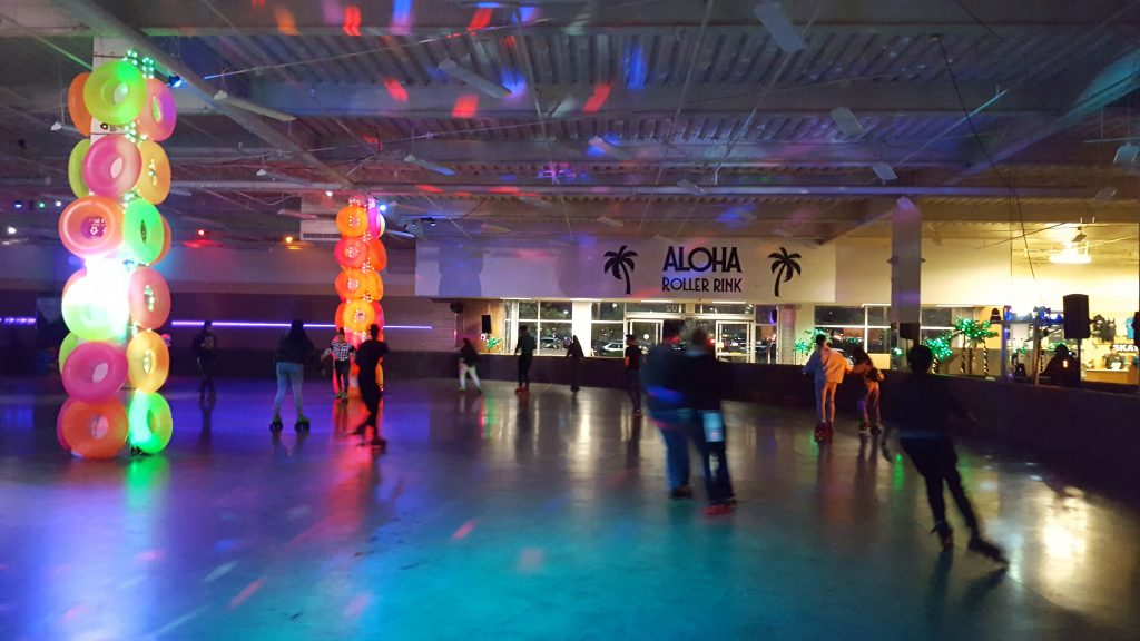 Interior shot of the Aloha Roller Rink with illuminated poles covered with brightly colored inner tubes.